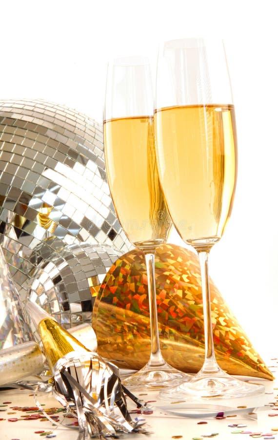 Vetro di Champagne con i cappelli del partito dell'oro fotografie stock
