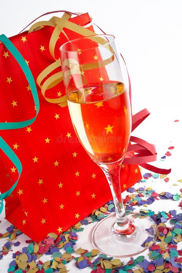 Vetro di Champagne con il sacchetto di acquisto rosso fotografie stock libere da diritti