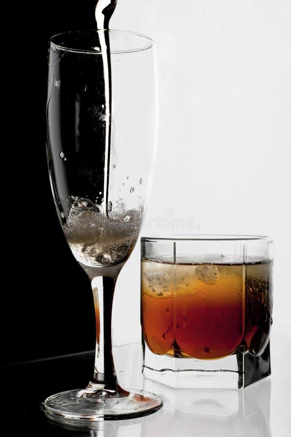 Vetro di champagne e di whisky con ghiaccio. fotografie stock
