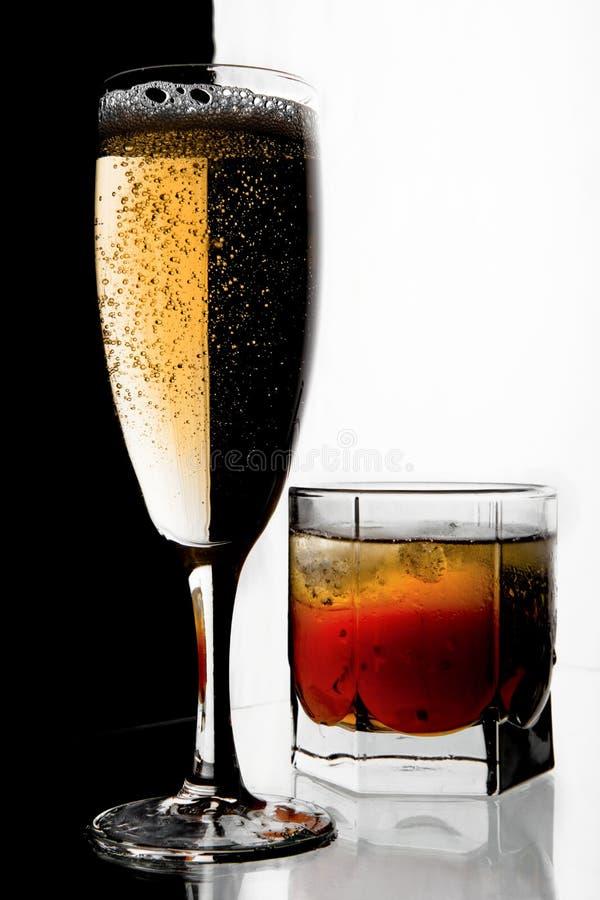 Vetro di champagne e di whisky con ghiaccio. immagini stock