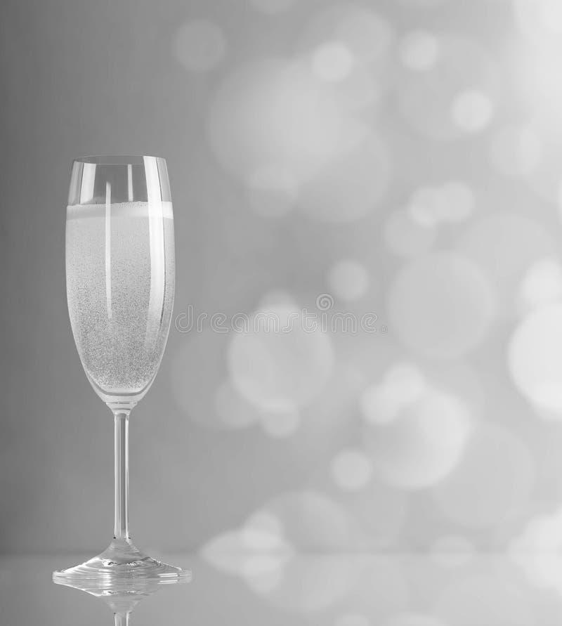 Vetro di champagne in un colore in bianco e nero contro i cerchi luminosi immagini stock libere da diritti