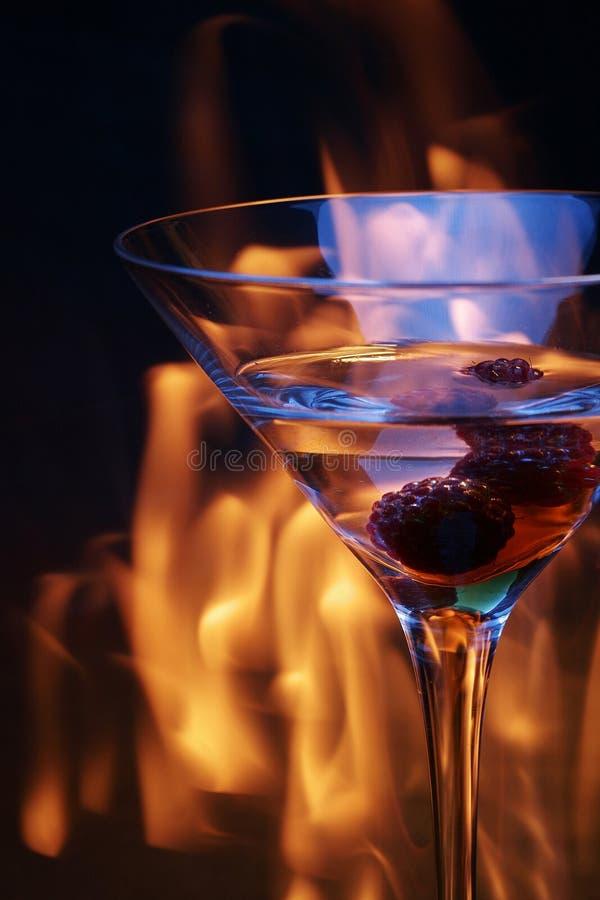 Vetro di cocktail sopra la traccia del fuoco fotografia stock libera da diritti
