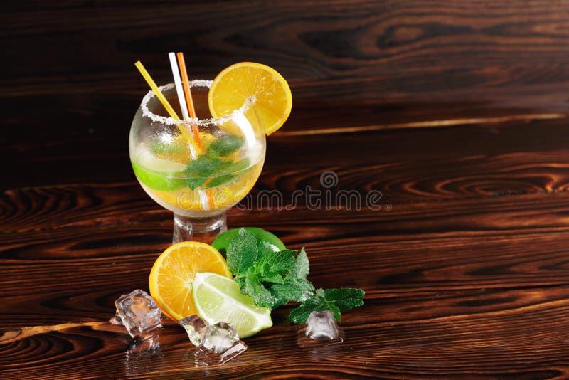 Vetro di cocktail di una bevanda fredda su un fondo di legno Agrumi e ghiaccio per una scossa Concetto del menu del caffè Copi lo immagine stock