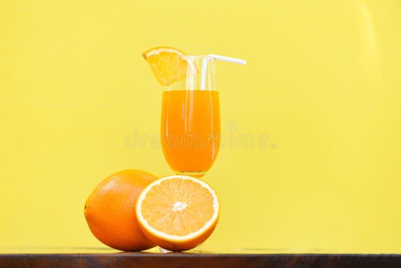 Vetro di estate del succo d'arancia con la frutta arancio del pezzo con giallo fotografia stock