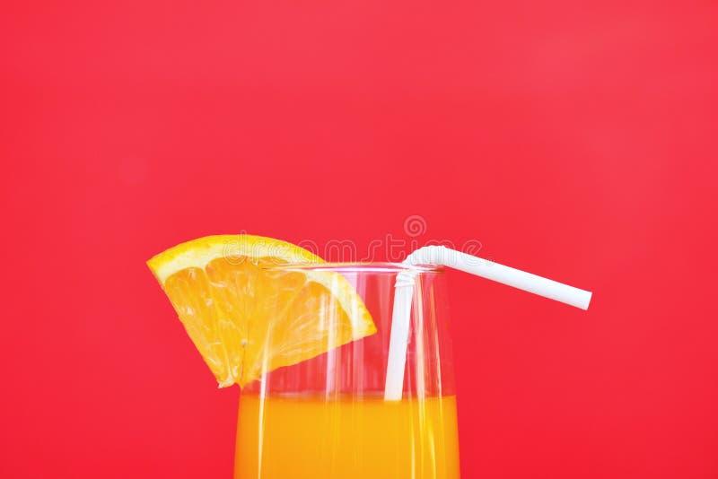 Vetro di estate del succo d'arancia con la frutta arancio del pezzo su fondo rosso immagine stock
