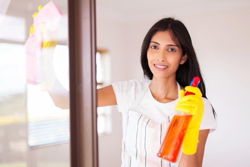 Vetro di finestra di pulizia della casalinga immagini stock libere da diritti