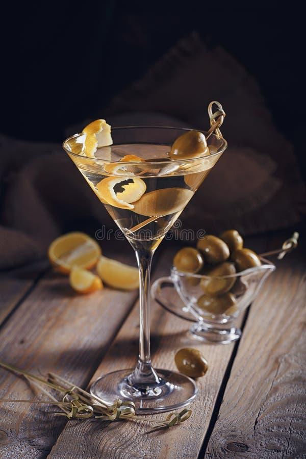 Vetro di martini con le olive verdi su una vecchia tavola di legno immagine stock libera da diritti