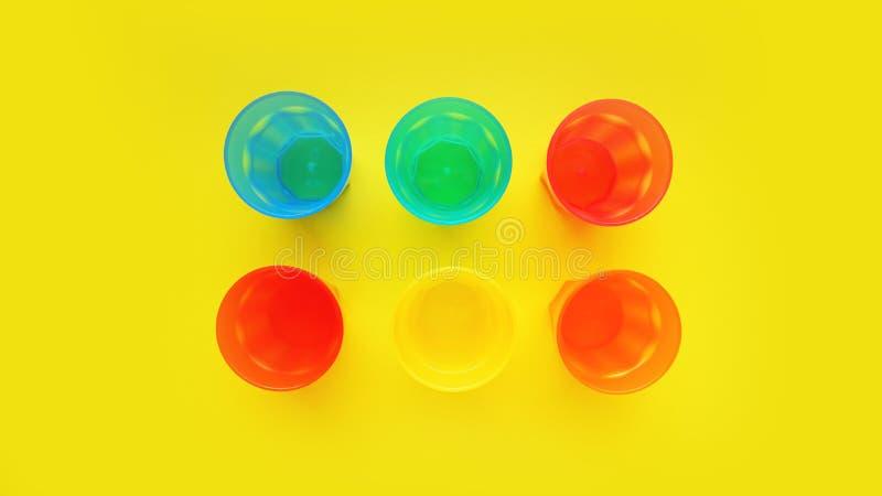Vetro di plastica di vario colore isolato su fondo giallo immagine stock libera da diritti