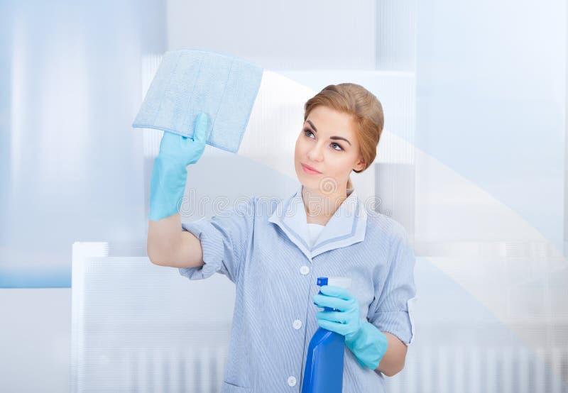 Vetro di pulizia della domestica felice fotografie stock libere da diritti