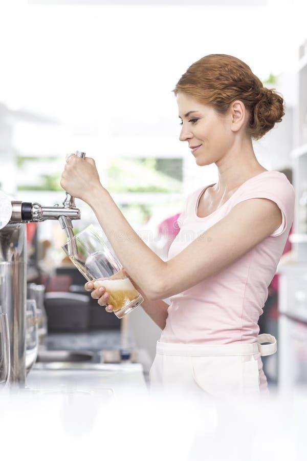Vetro di riempimento sorridente della giovane cameriera di bar dal rubinetto della birra al ristorante fotografia stock libera da diritti
