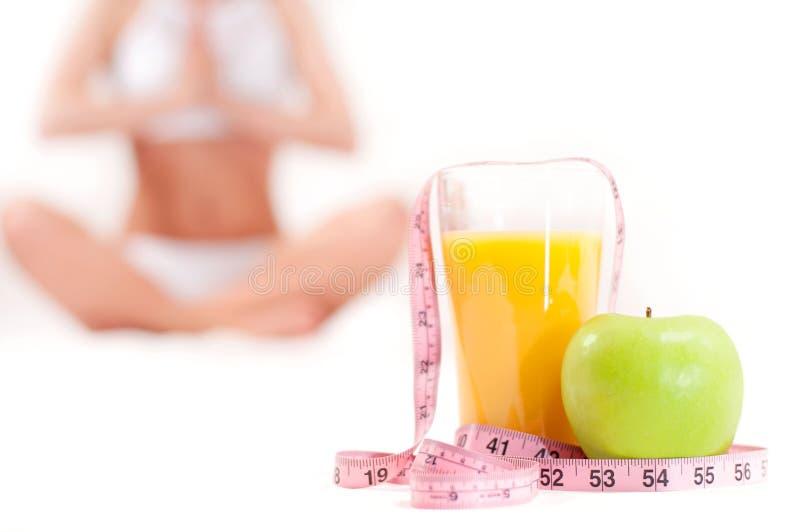 Vetro di succo d'arancia con la mela verde e nastro adesivo di misurazione fotografie stock libere da diritti