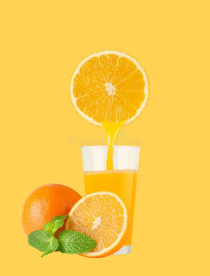 Vetro di succo d'arancia con le arance su fondo giallo pastello immagine stock
