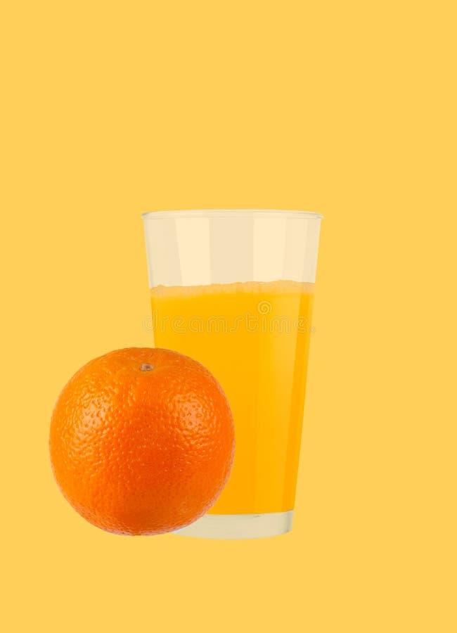 Vetro di succo d'arancia con le arance su fondo giallo pastello immagine stock libera da diritti