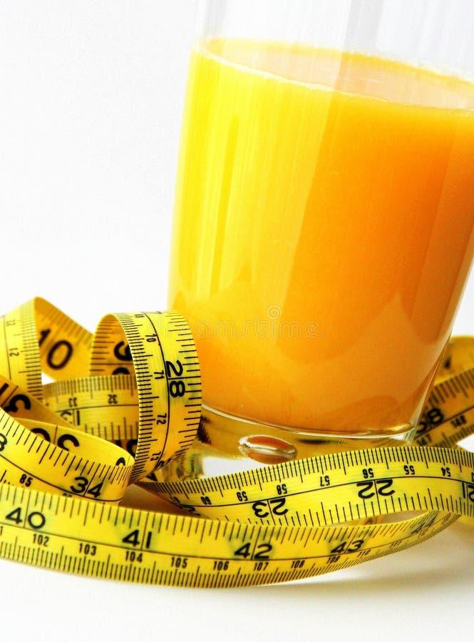 Vetro di succo d'arancia e del nastro di misurazione immagini stock