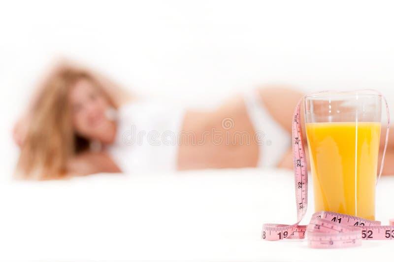 Vetro di succo d'arancia e del nastro di misurazione fotografie stock