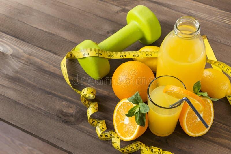 vetro di succo d'arancia, arancia, limone, bottiglia del succo, zantel verde, nastro di misurazione su fondo marrone di legno immagine stock