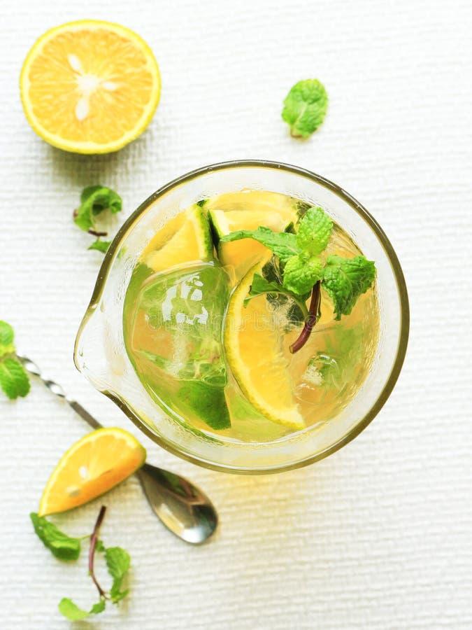 Vetro di tè arancio fresco con la foglia della menta su fondo bianco immagine stock