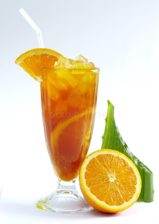 Vetro di tè arancio fresco con la foglia di vera dell'aloe su backgroun bianco immagini stock libere da diritti
