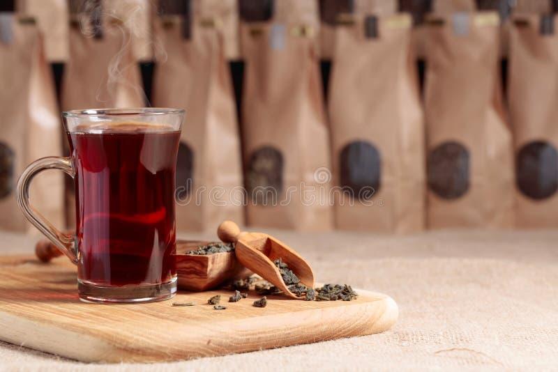 Vetro di tè caldo Cucchiaio di legno con le foglie di tè secche Pacchetto della carta del mestiere con la finestra per tè sciolto immagini stock
