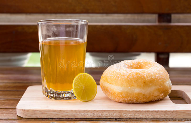 Vetro di tè con il limone e la ciambella dolce immagini stock