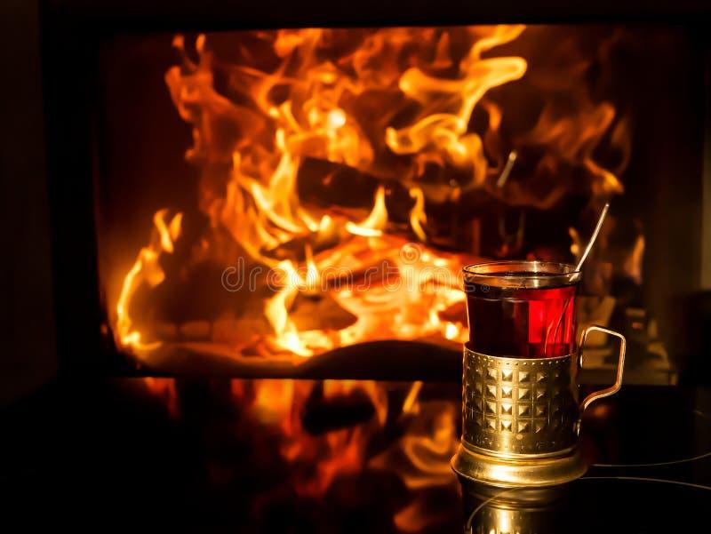 Vetro di tè nel supporto di tazza dal camino fotografie stock libere da diritti