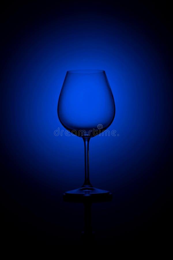 Vetro di vino alto vuoto sul nero e su un fondo blu immagini stock libere da diritti