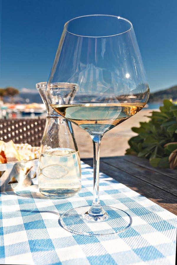 Vetro di vino bianco con una caraffa di acqua sulle rive del mar Mediterraneo in Italia immagini stock libere da diritti