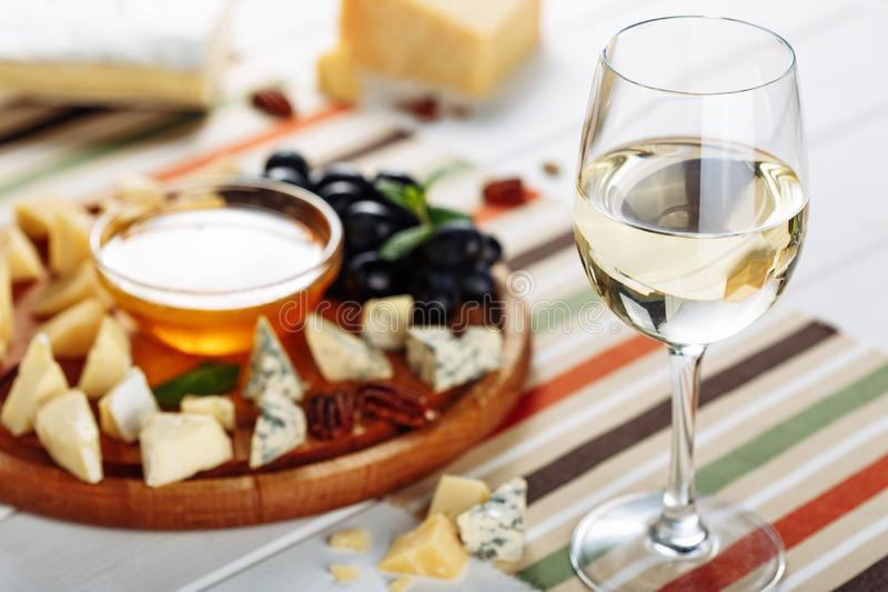 Vetro di vino bianco, del piatto di formaggio con il mozarella, del parmigiano, del miele e delle olive sulla tavola Fuoco selett immagine stock libera da diritti