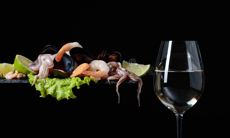 Vetro di vino bianco e di frutti di mare deliziosi misti fotografie stock libere da diritti