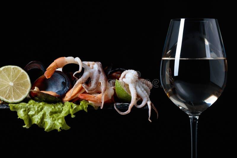 Vetro di vino bianco e di frutti di mare deliziosi misti fotografie stock
