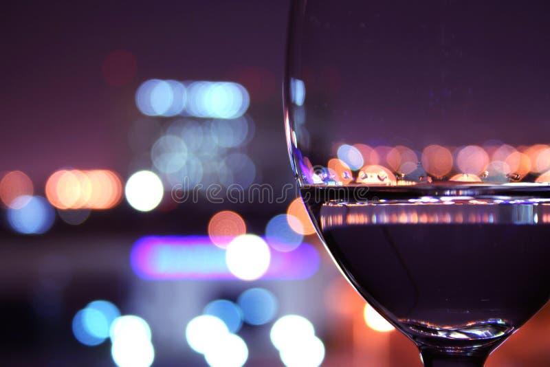 Vetro di vino con gli indicatori luminosi vaghi immagini stock libere da diritti