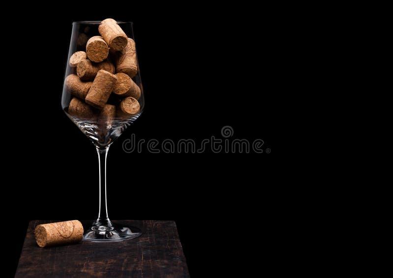 Vetro di vino con i sugheri dentro con sughero accanto a vetro sul bordo di legno su fondo nero Spazio per testo immagini stock libere da diritti