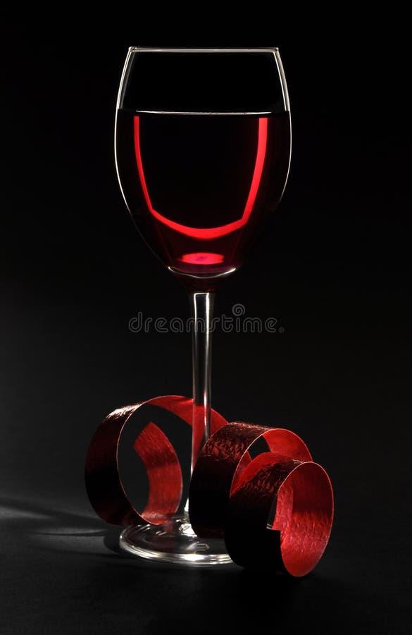 Vetro di vino con il nastro sul nero immagine stock