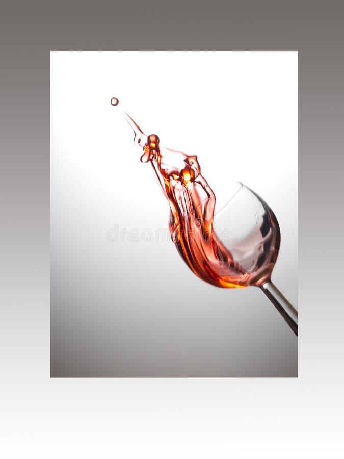 Vetro di vino con la spruzzata della rosa nel telaio immagine stock