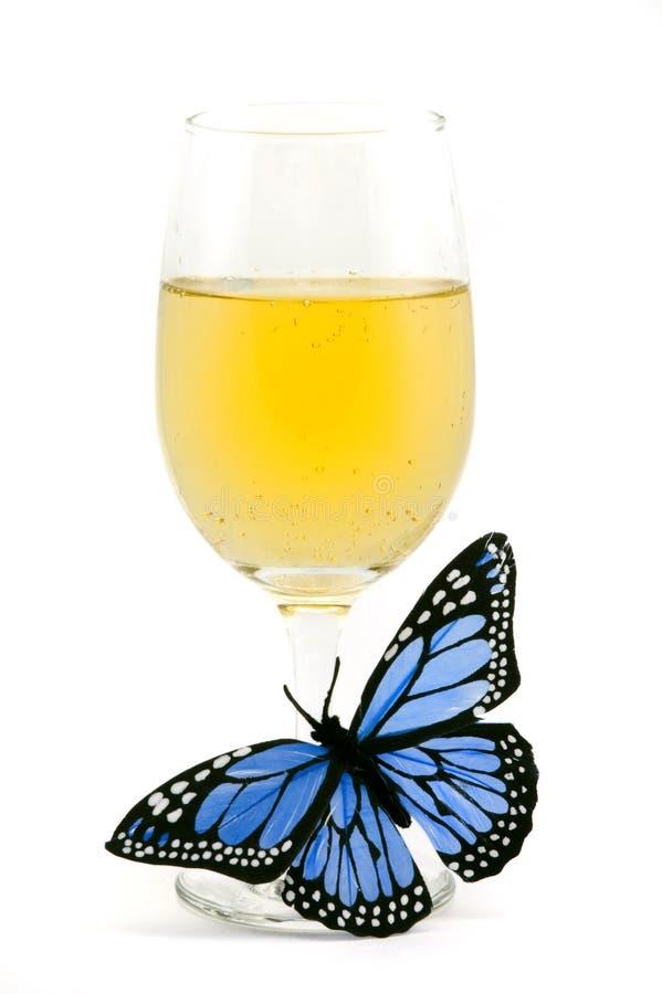 Vetro di vino riempito e farfalla blu immagine stock