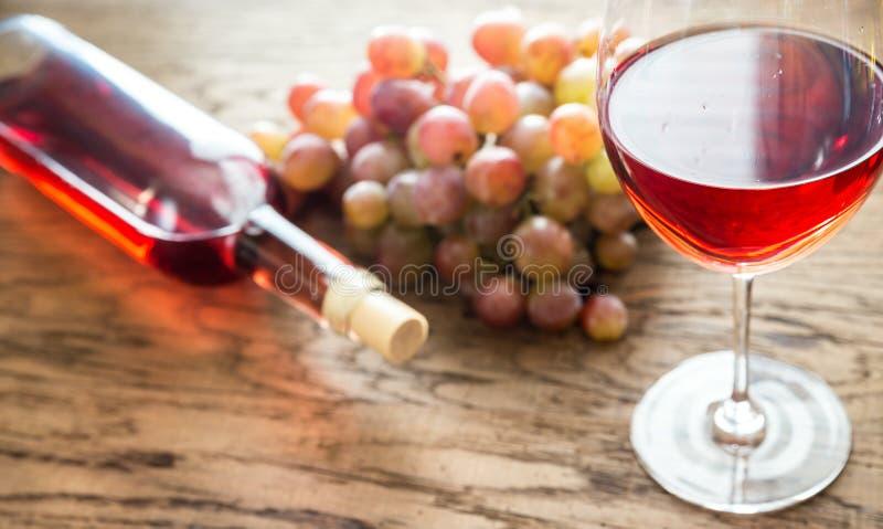 Vetro di vino rosato con il mazzo di uva immagini stock libere da diritti