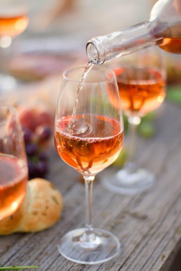 Vetro di vino rosato sulla tavola di picnic immagini stock libere da diritti