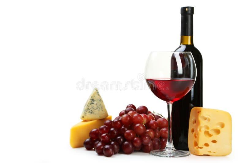 Vetro di vino rosso, di formaggi e dell'uva isolati su un bianco fotografia stock