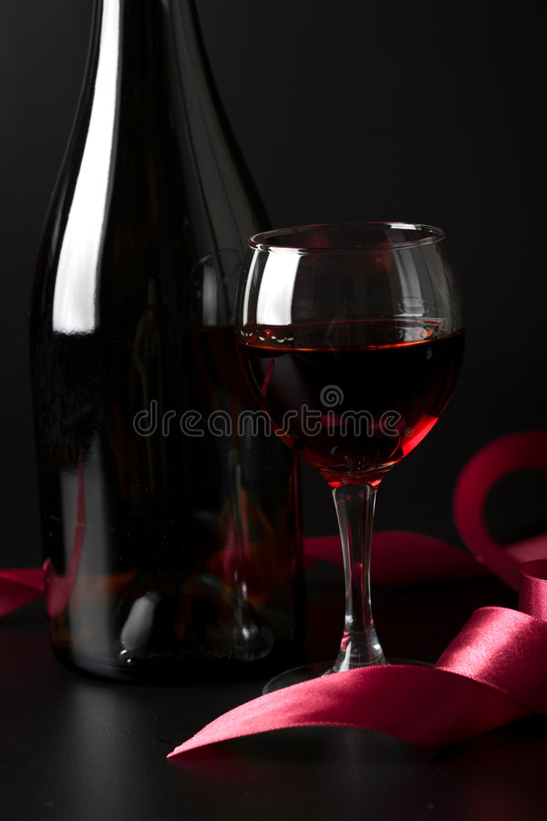 Vetro di vino rosso e del nastro rosso sopra il nero immagine stock