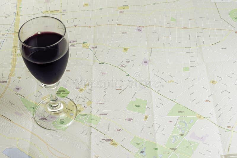 Vetro di vino sulla mappa per effettuare pianificazione di viaggio fotografia stock libera da diritti