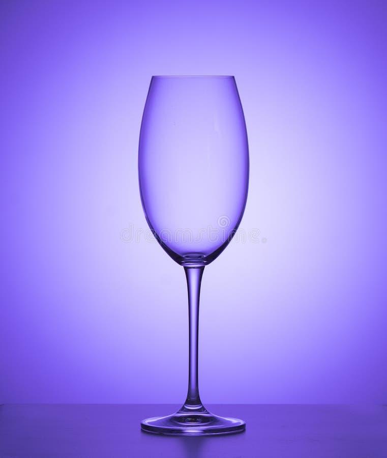 Vetro di vino vuoto su un fondo porpora Fine in su fotografie stock libere da diritti