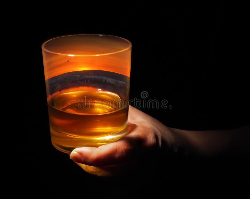 Vetro di whiskey con una vista di sera della città dentro immagini stock libere da diritti