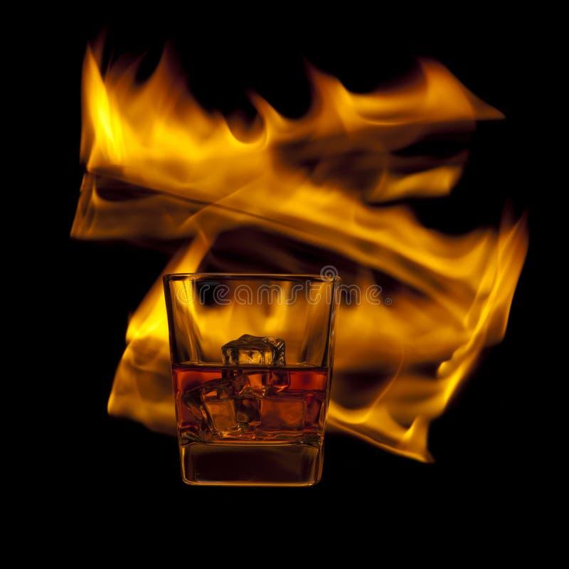Vetro di whiskey e di fuoco immagine stock libera da diritti