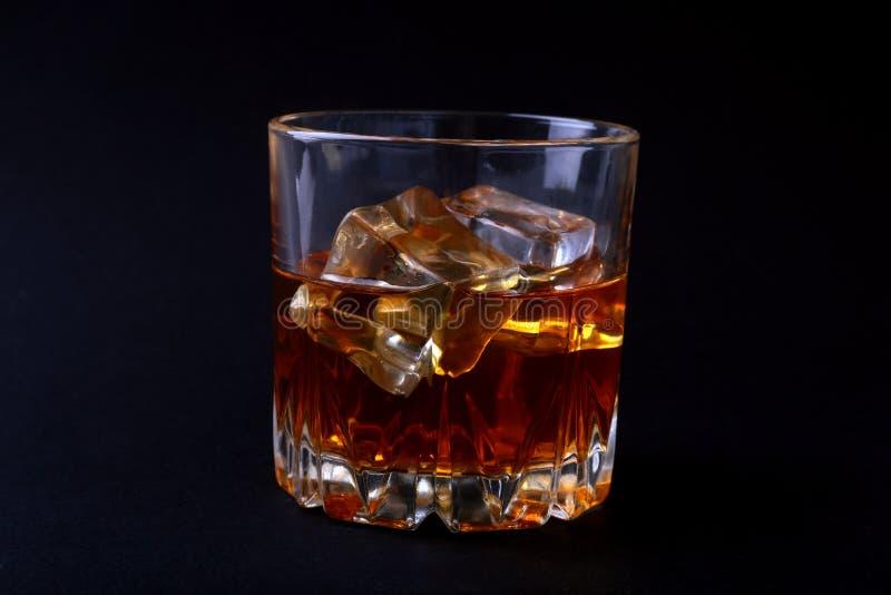 Vetro di whiskey o di bourbon con ghiaccio sulla tavola di pietra nera fotografie stock