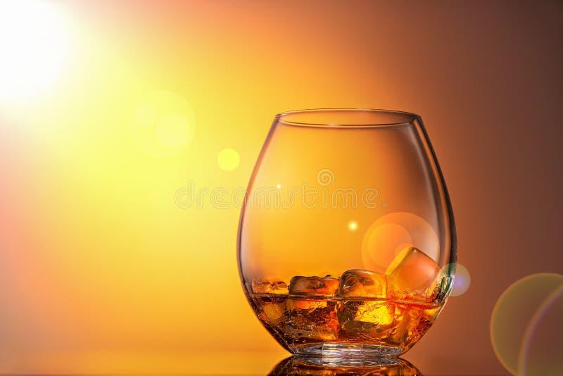 Vetro di whiskey scozzese con ghiaccio su un fondo arancio, è illuminato da luce solare Chiuda su, copi lo spazio immagine stock libera da diritti