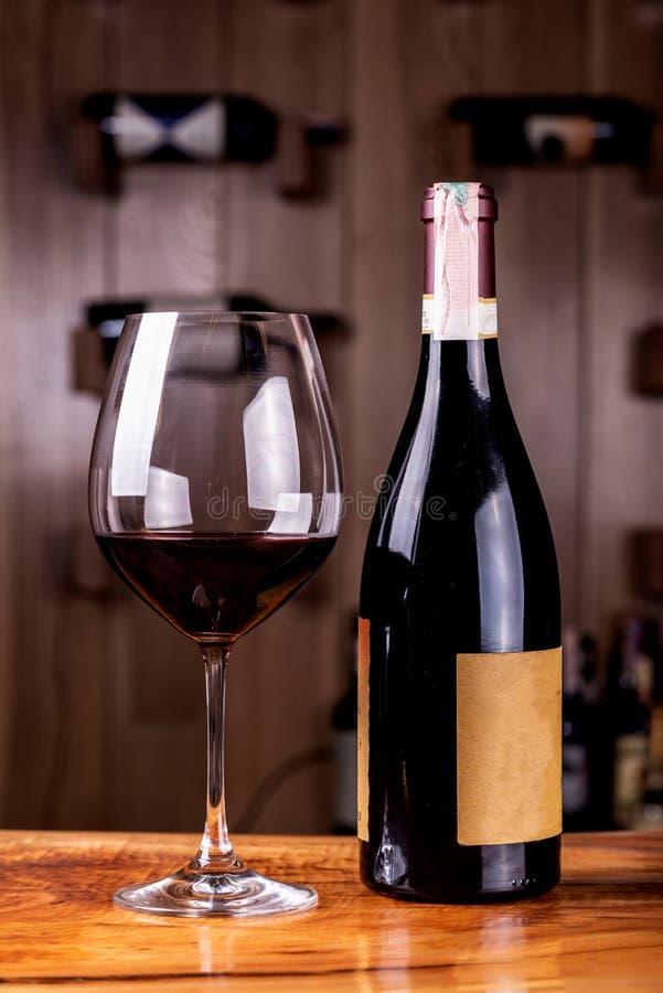 Vetro e bottiglia con vino rosso delizioso sulla tavola di legno Nelle bottiglie del vino rosso del fondo impilate sugli scaffali fotografie stock