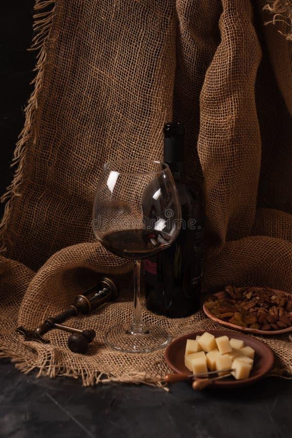 Vetro e bottiglia di vino rosso con formaggio, l'uva passa ed i dadi su tela di sacco, fondo scuro fotografie stock libere da diritti