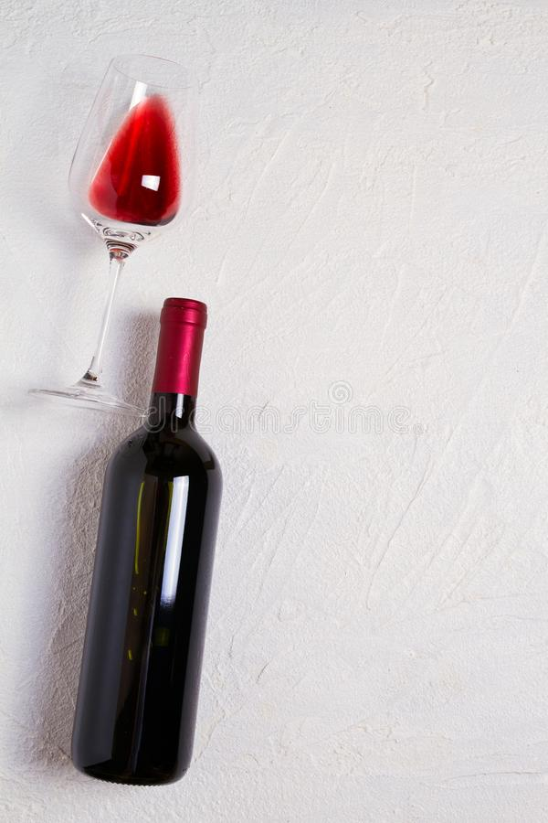 Vetro e bottiglia di vino rosso su priorità bassa bianca Del vino vita ancora vista superiore, verticale immagini stock
