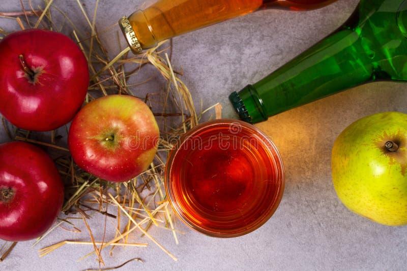 Vetro e bottiglie del sidro della pera e della mela con i frutti immagini stock libere da diritti