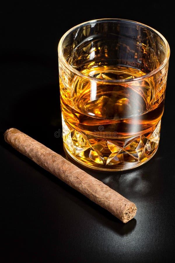 Vetro e sigaro del whisky fotografia stock